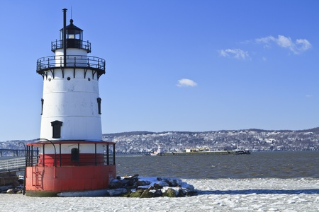 A barge head sup the icy Hudson River behind the Sleepy Hollow Lighthouse