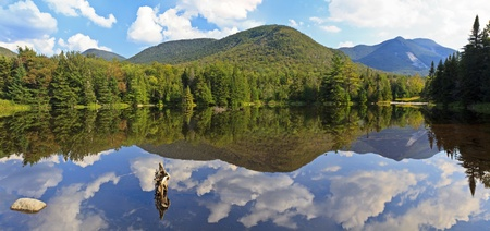 Panoramic view of Phelps Mtn, Mt Marcy and Mt. Colden reflected in Marcy Dam Pond in the High Peaks region of the Adirondack Mountains of New York