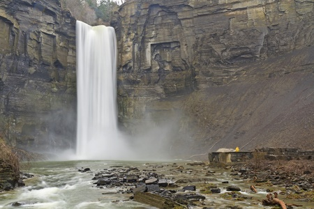 A person in a yellow raincoat gives perspective to towering 215 tall Taughannock falls near Ithaca, New York photo