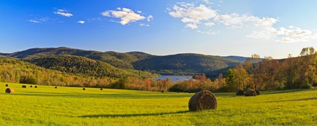 watershed: Panorama of a field of hay bales above the Pepacton Reservoir, surrounded by the Catskills Mountains of New York in the Autumn. Stock Photo