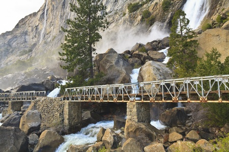 Misty Wapama Falls divides and spills under a footbridge and between boulders before falling into the Hetch Hetchy Reservoir in Yosemite National Park, California