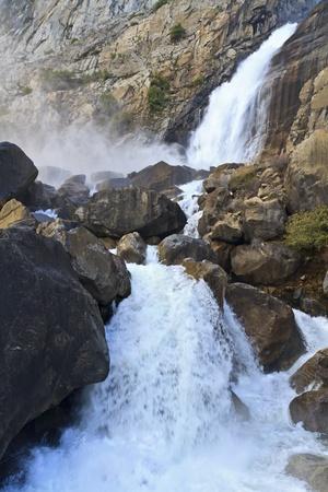 Wapama Falls kicks up clouds of mist as it spills between boulders in Spring in Yosemite National Park, California photo