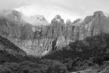 Black and white image of the Towers of the Virgin peaks shrouded in early morning clouds in  Zion National Park, Utah photo