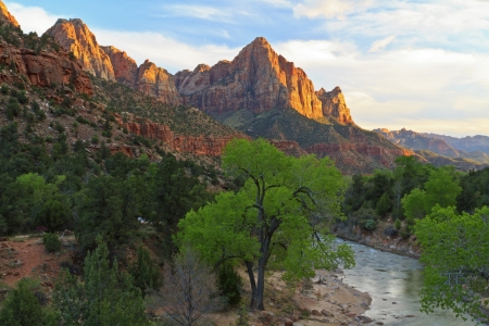 The last rays of sun hit The Watchman mountain with the Virgin River in the foreground in ZIon National Park, Utah