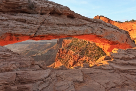 The bottom of Mesa Arch glows red just after Sunrise in Canyonlands National Park in Utah