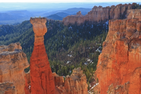 Early morning light in Agua Canyon lights up The Hunter hoodoo with blue-green mountains behind in Bryce Canyon National Park, Utah photo