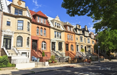 A row of unique townhouse apartment buildings with stoops on New York Ave. in the Crown Heights neighborhood of Brooklyn, NY photo