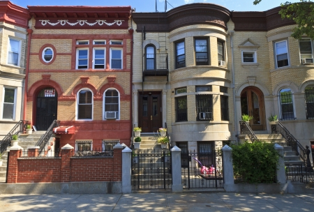 brownstone: A row of attached brick apartment buildings with stoops on Lincoln Place in the Crown Heights neighborhood of Brooklyn, NY Stock Photo