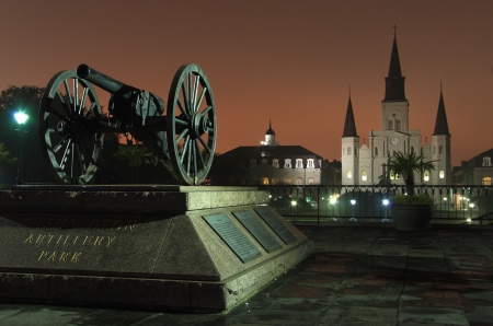 The lights from Bourbon Street reflect off the fog and silhouette St. Louis Cathedral and a vintage canon in the French Quarter of New Orleans, LA Standard-Bild