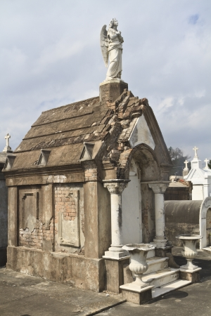 An angel statue sits atop a tomb in Lafayette Cemetery #2 in New Orleans, Louisiana