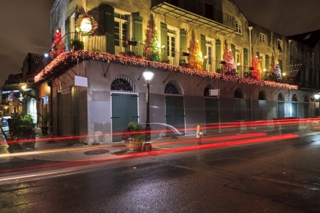 Tail lights streak by a building on the corner of Barrcks St and French Market Place festooned with Christmas decorations in the French Quarter of New Orleans