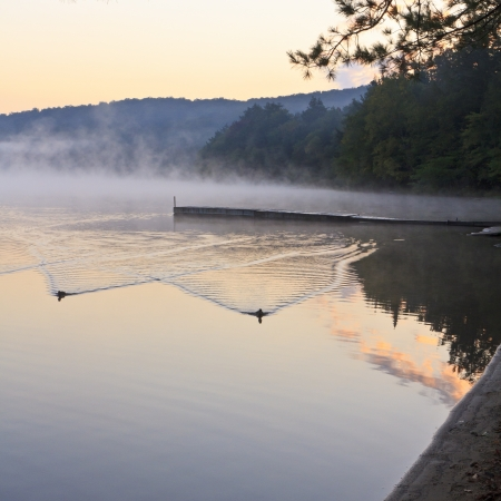 Foggy sunrise on serene Eighth Lake in the Fulton Chain Lakes in the Adirondacks Mountains of New York photo