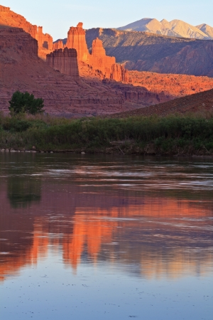 The Fisher Towers partially lit by the late afternoon sun reflected in the Colorado River near Moab,Utah