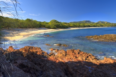 HDR image of quiet, beautiful sand and rocks of Playa Conchal and the azure waters of the Pacific Ocean in Guanacaste, Costa RIca Standard-Bild