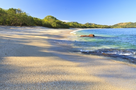 Sand and shells on Playa Conchal and the azure waters of the Pacific Ocean in Guanacaste, Costa RIca