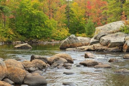 Bomen en rotsen op een eiland tot uiting in een rivier Moose in de Adirondack Mountains van New York (Panorama)