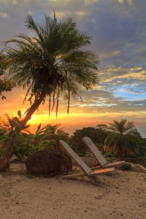 Empty chairs under a plam tree on a poolside 'beach' overlooking the Pacific Ocean and Nicoya Peninsula at sunset near Tarcoles, Costa Rica