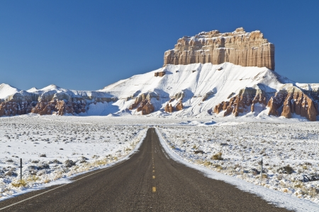 covered fields: Road thru snow covered fields headed toward Wild Horse Butte near Goblin Valley State Park, Utah Stock Photo
