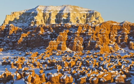 marge: Late afternoon sun hits odd rock formations and a marge sandstone mesa in Goblin Valley State Park, Utah Stock Photo