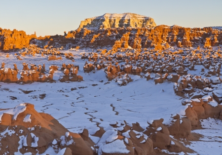 goblins: Late afternoon sun hits a string of odd rock formations amid the snow in Goblin Valley State Park, Utah