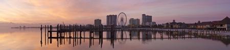 Panoramic photo of sunrise on the on Santa Rosa Sound and Pensacola Beach ferris wheel in Pensacola Beach, Florida