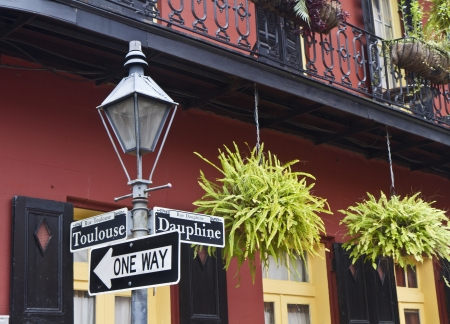 sign post: Ferns hang from a balcony railing on the corner of Toulouse and Dauphine in the French Quarter of New Orleans, Louisiana Stock Photo