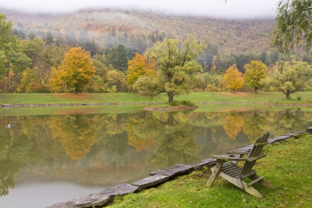 rockwall: An Adirondack style wooden chair on the bank of a misty Autumn pond in the Catskills Mountains in Big Indian, NY Stock Photo