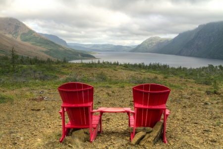 morne: A pair of adirondack chairs at the Trout River Pond viewpoint, with the Tablelands and cliffs lining foggy Trout River Pond in Gros Morne National Park, Newfoundland
