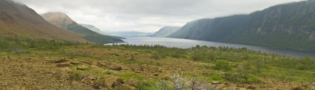 Panoramic view of the Tablelands and cliffs lining foggy Trout River Pond in Gros Morne National Park, Newfoundland photo