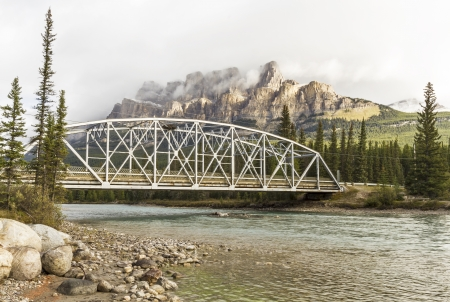 Castle Mountain emerges from the clouds above a bridge over the Bow River in Banff National Park, Alberta photo
