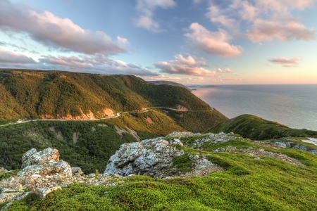 nova scotia: The winding Cabot Trail road seen from high above on the Skyline Trail at sunset in Cape Breton Highlands National Park, Nova Scotia