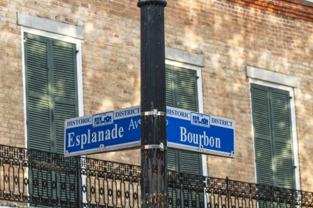 A street sign at the corner of Bourbon Street and Esplanade Avenue against a brick wall in the French Quarter of New Orleans, Louisiana photo
