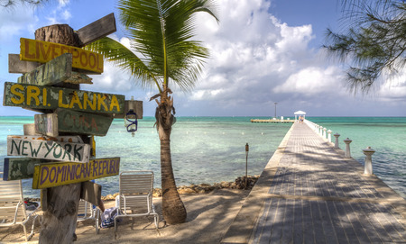 cayman: A signpost with various destinations next to the blue-green crystal clear waters off Rum Point dock on the north side of Grand Cayman, Cayman Islands, BWI