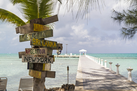 A signpost with various destinations next to the blue-green crystal clear waters off Rum Point dock on the north side of Grand Cayman, Cayman Islands, BWI