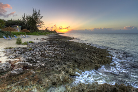 cayman islands: The sun sets over a rocky coast on Boatswains Bay on the north side of Grand Cayman, Cayman Islands, BWI Stock Photo