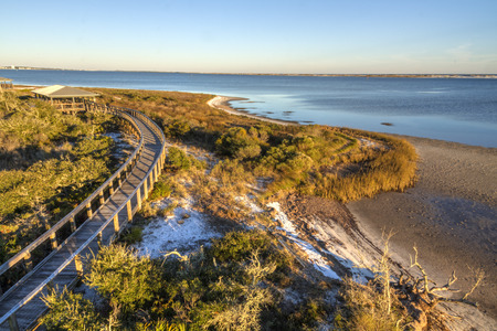 A boardwalkcurves over the vegetation on the dunes in Big Lagoon State Park near Pensacola, Florida