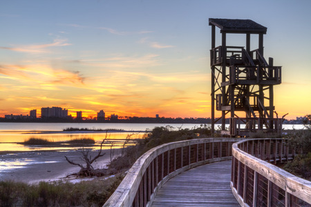 A wildlife observation tower silhouetted against a Perdido Key sunset in Big Lagoon State Park near Pensacola, Florida