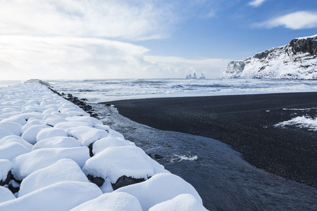 Basalt black sands and a rock jetty covered with fresh snowfall at Vík í Mýrdal on the South coast of Iceland photo