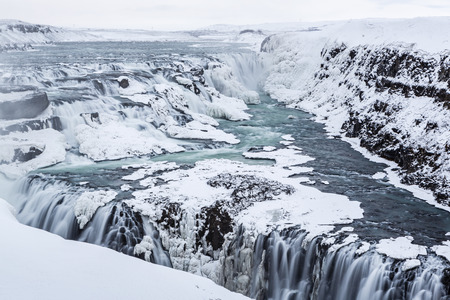 Majestic Gullfoss waterfalls form a half frozen triangle as the Hvita River falls into a wintry gorge in Western Iceland