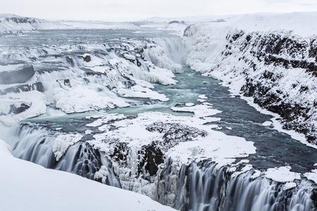 Majestic Gullfoss Wasserfälle bilden ein Dreieck als die Hälfte der zugefrorenen Fluss Hvita fällt in einen winterlichen Schlucht in West-Island Standard-Bild - 26746103