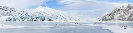 Panoramic view of the aqua blue tongue of Heinabergs glacier and frozen glacial lagoon in Southeast Iceland near Hofn photo
