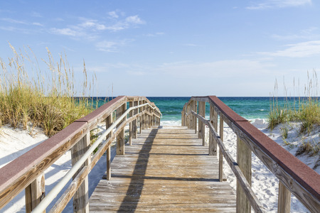 The boardwalk leads tro the turquoise waters of the Gulf of Mexico at Park West on the western end of Pensacola Beach, Florida.