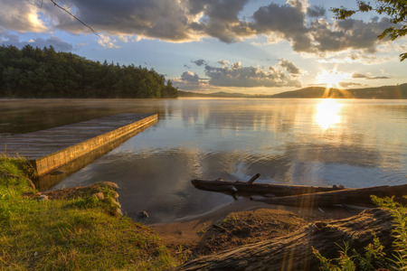 Sunset on the shore of Seventh Lake in the Fulton Chain Lakes region of the Adirondack Mountains of New York Standard-Bild