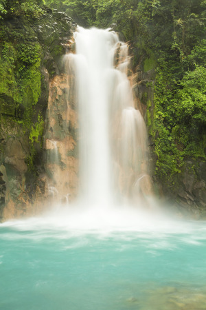 The cerulean blue waters of the Rio Celeste Waterfall in Volcan Tenorio National Park, Costa Rica.