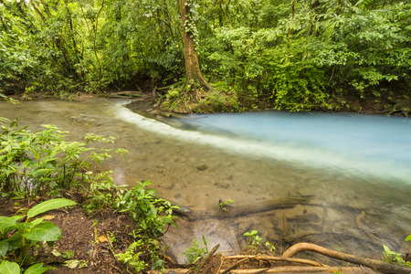 reacts: Sulphur from one stream reacts with sediment from another to form the Cerulena blue waters of the Rio Celeste in Volcan Tenorio National Park, Costa Rica. Stock Photo