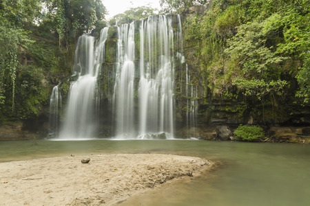 A sandy beach at a popular swimming hole at Llanos de Cortés waterfall near Bagaces, Costa Rica