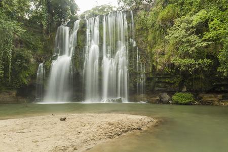 A sandy beach at a popular swimming hole at Llanos de Cortés waterfall near Bagaces, Costa Rica