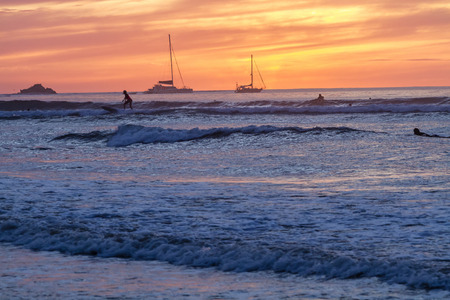 Surfers silouetted against the setting sun on Playa Tamarindo, Guanacaste, Costa Rica