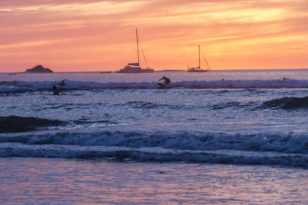 brilliantly: Surfers silhouetted against a brilliantly colored sunset