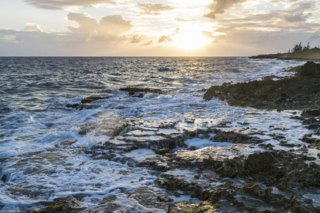 settles: Foam settles around the famous Blow Holes on the south coast of Grand Cayman against the setting sun. Stock Photo